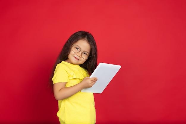 Schönes emotionales kleines mädchen lokalisiert auf rotem raum. halblanges porträt eines glücklichen kindes, das eine geste zeigt und nach oben zeigt. konzept des gesichtsausdrucks, der menschlichen gefühle, der kindheit.