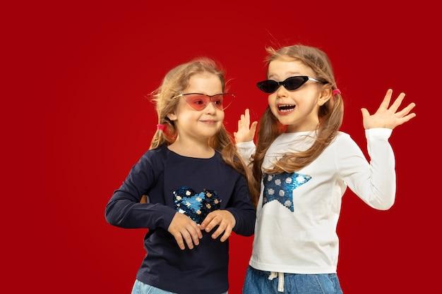 Schönes emotionales kleines mädchen lokalisiert auf rotem raum. halblanges porträt von glücklichen schwestern oder freunden in roter und schwarzer sonnenbrille