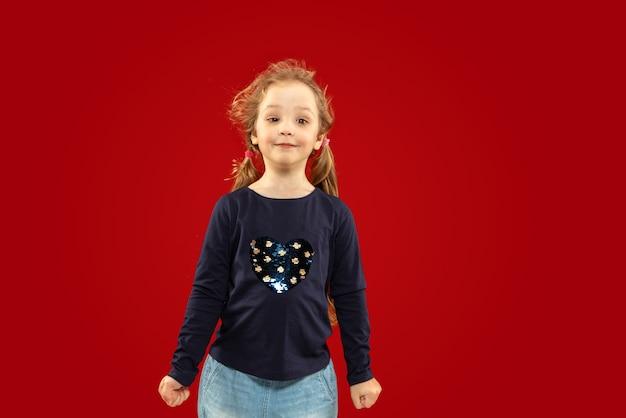 Schönes emotionales kleines mädchen lokalisiert auf rotem studio