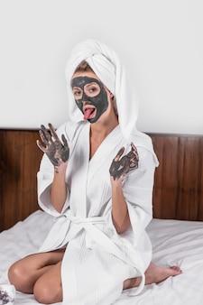 Schönes emotionales mädchen, das in einer tonmaske mit tonhänden in einem weißen bademantel und einem handtuch auf ihrem kopf auf dem bett sitzend aufwirft. zunge zeigen.