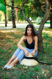 Schönes emotionales mädchen, das unter einem baum im park sitzt, gesichtsausdruck von ressentiments und enttäuschung. grimassen