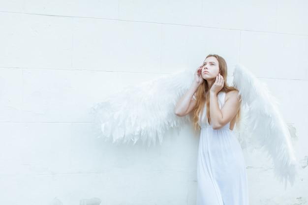 Schönes engelsmädchen mit weißen flügeln nahe der wand, die nachdenklich nach oben schaut