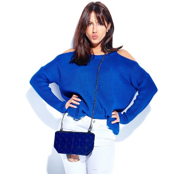 Schönes ernstes hipsterbrünettfrauenmodell im lässigen stilvollen sommerpullover und in der blauen handtasche lokalisiert auf weißem hintergrund