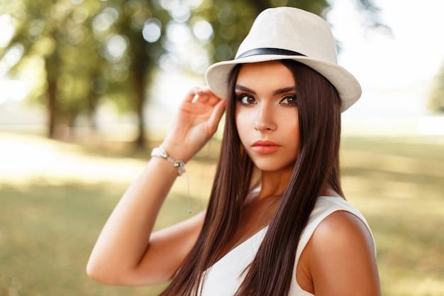 Schönes ernstes mädchen mit make-up im weißen kleid an einem sommertag im park