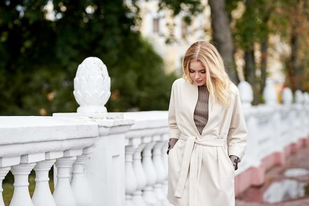 Schönes ernstes stilvolles modisches kluges mädchen, geht auf der brücke. charmante fröhliche glückliche blonde frau in einem weißen mantel.