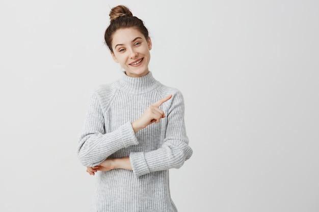 Schönes erwachsenes mädchen lächelnd zeigt finger zur seite. weiblicher enthusiast, der ihre präferenz mit fingergeste darstellt. glück und konzept genießen