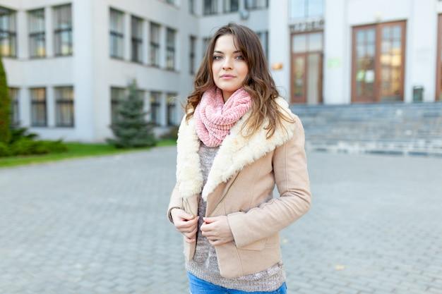 Schönes europäisches mädchen gekleidete warme herbstkleidung geht straßen mit bürogebäuden