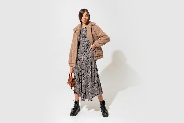 Schönes europäisches modell in stilvollem pelzmantel und kleid. stiefelette aus schwarzem leder. braune handtasche halten.