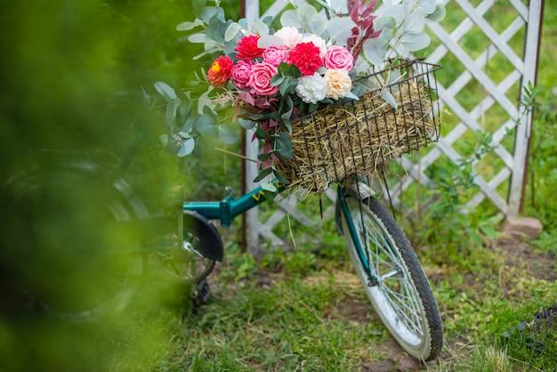 Schönes fahrrad mit blumen in einem korb steht auf einer allee in einem park bei sonnenuntergang