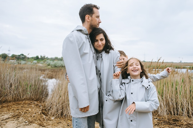 Schönes familienportrait gekleidet im regenmantel nahe dem see