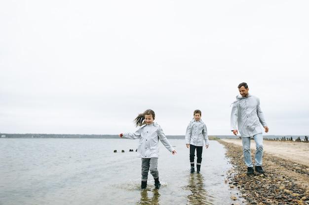 Schönes familienportrait gekleidet in raincoatnear das meer