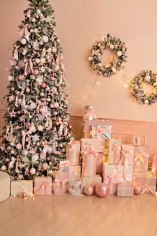 Schönes festlich dekoriertes rosa zimmer mit einem weihnachtsbaum, geschenke. neujahr.