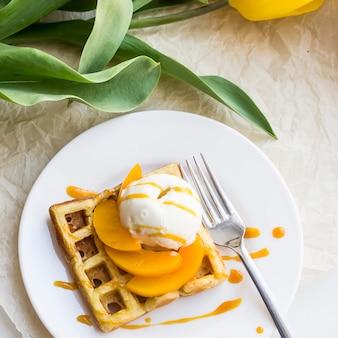 Schönes festliches belgisches waffelfrühstück nahe bei einer gelben tulpe