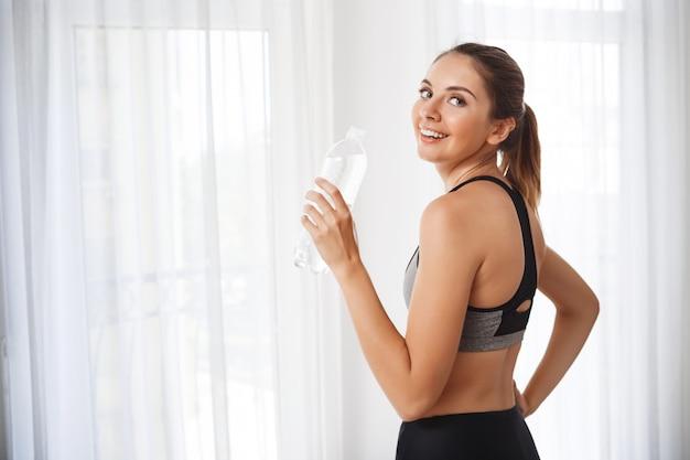 Schönes fitness-mädchen mit wasserflasche vor dem fenster