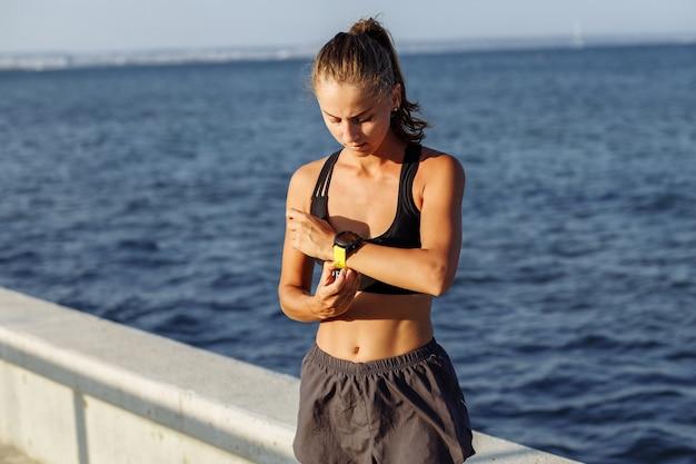 Schönes fitness-mädchen trägt eine smartwatch, bevor sie am meer rennt