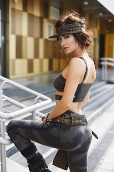 Schönes fitness-modell-mädchen mit perfektem sexy körper im modischen outfit mit militärischem muster, das draußen am städtischen hintergrund aufwirft