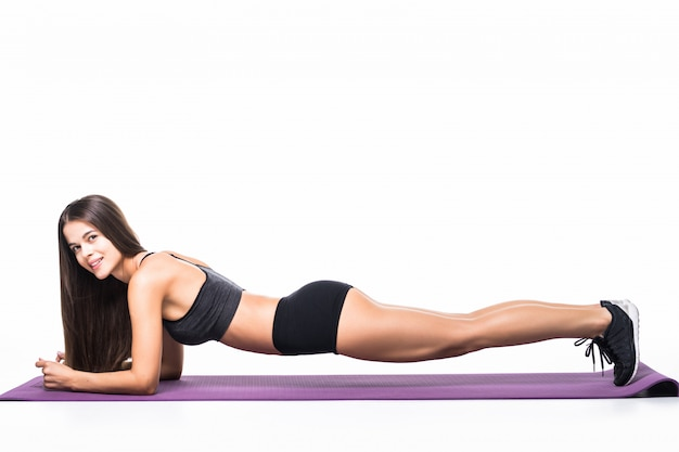 Schönes fitnessmädchen in der sportbekleidung, die eine planke auf weiß ausübt