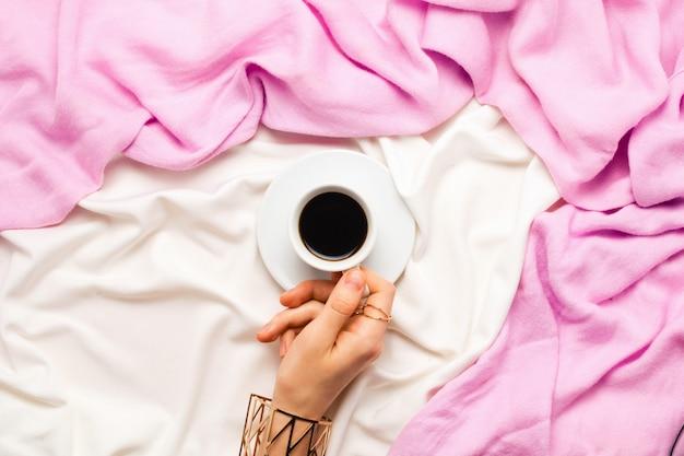 Schönes flatlay mit der hand der frau, die eine tasse morgenkaffee im bett hält. draufsicht