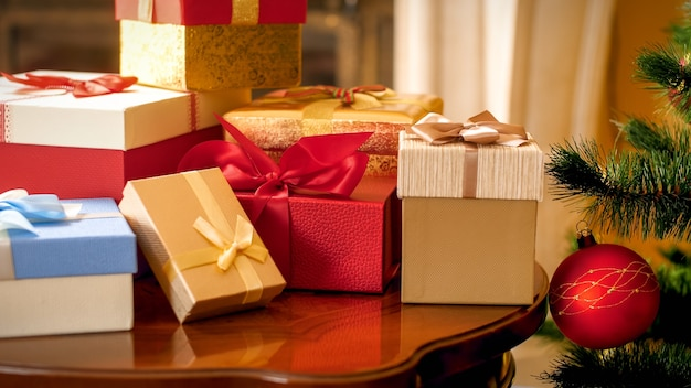Schönes foto der nahaufnahme von einem großen haufen weihnachtsgeschenke und -geschenke in kisten, die auf einem holztisch im wohnzimmer gegen weihnachtsbaum und kamin stehen