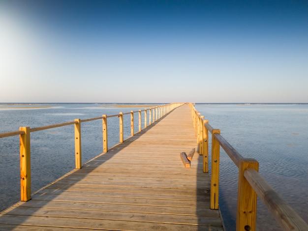 Schönes foto des langen hölzernen piers oder der brücke im ozean