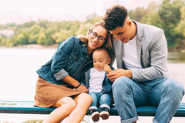 Schönes foto einer jungen familie, die spaß auf einer bank nahe einem see im park hat
