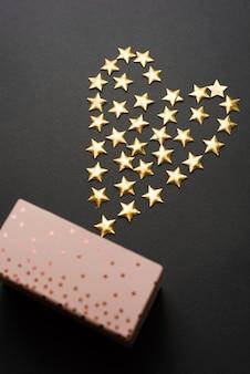 Schönes foto eines geschenks und darüber einige kleine sterne, die in einem herzen geformt sind
