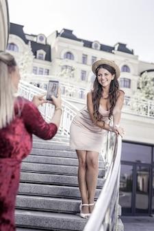 Schönes foto. nette entzückte frau, die auf der treppe steht, während sie ihre freundin ansieht
