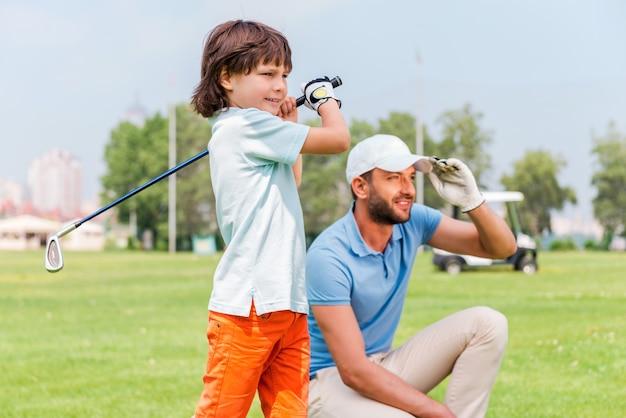 Schönes foto! selbstbewusster kleiner junge, der golf spielt, während sein vater auf dem golfplatz neben ihm steht