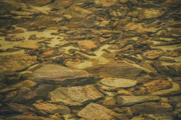Schönes fragment des orangefarbenen steinbodens des bergsees mit transparentem wasser. bunter minimalistischer naturhintergrund mit vielen orangefarbenen steinen mit moosen und flechten auf dem grund des bergsees.