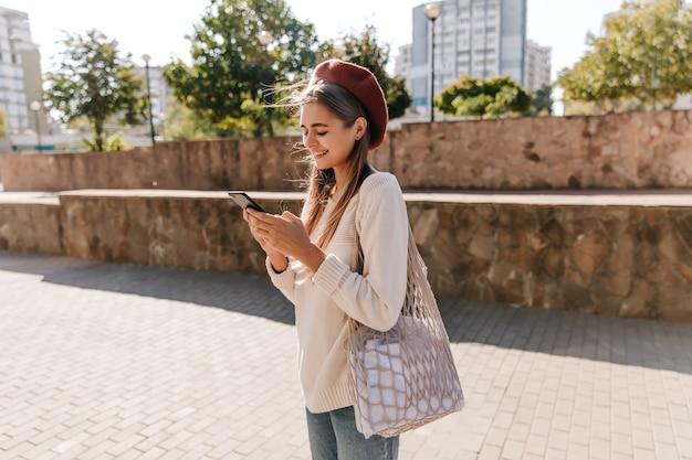 Schönes französisches mädchen mit tasche, die auf der straße im sonnigen herbsttag steht. jocund dame in lässiger kleidung sms-nachricht.