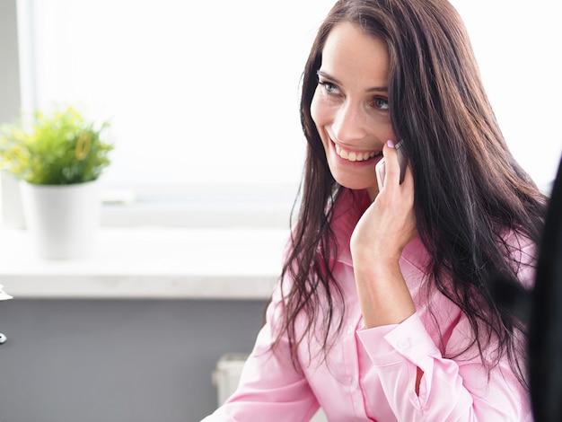 Schönes frauenbüro, das telefon spricht und lächelt. fehlende büroarbeit.