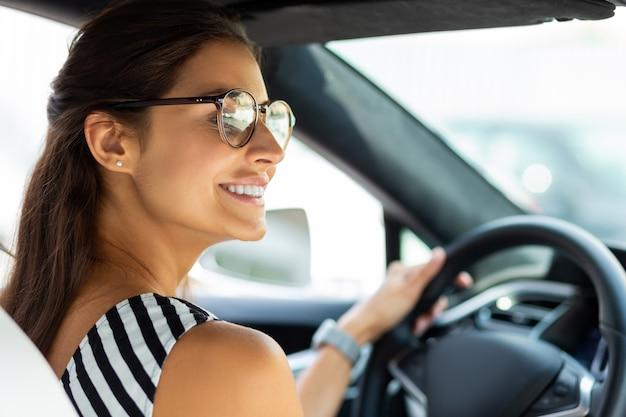 Schönes frauenfahren. schöne lächelnde frau, die ihr auto fährt und in den rechten seitenspiegel schaut