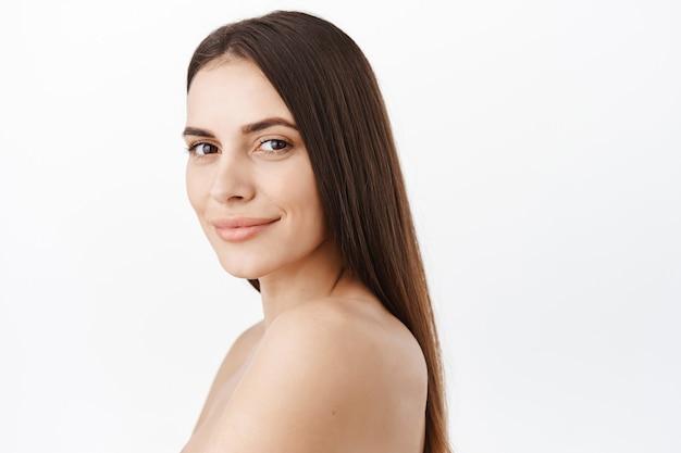 Schönes frauengesichtskosmetikkonzept, gesundes, natürliches, sauberes haut-nude-make-up, gesichtsbehandlung ohne falten, hydratisiert und glatt, lange perfekte haarsträhnen auf nacktem rücken, vorne lächelnd