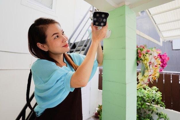 Schönes frauenhaus passt die richtungswinkelansicht der cctv-heimüberwachungskamera und die feinabstimmung der internetkamera für eine perfekte szene des zuschauens an. konzept für den selbstständigen und diy-job der modernen hausfrau.