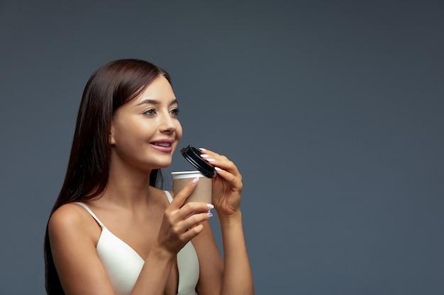 Schönes frauenmädchen genießt und bietet ein heißes getränk, einen tee oder einen kaffee in einem natürlichen wegwerfglas an.