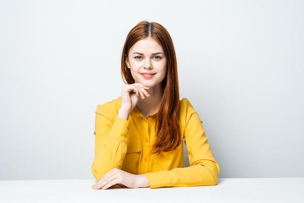 Schönes frauenmodell am tisch in einem gelben hemd wirft verschiedene emotionen auf