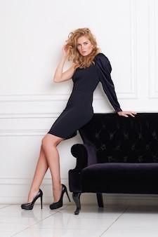 Schönes frauenmodell, das im eleganten kleid im studio aufwirft.