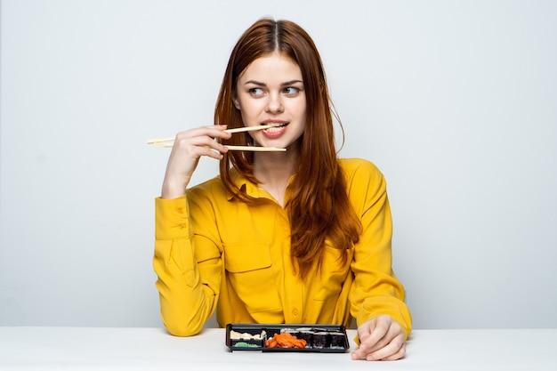 Schönes frauenmodell, das sushi und brötchen von der essenslieferung am tisch in einem gelben hemd isst, das verschiedene emotionen aufwirft