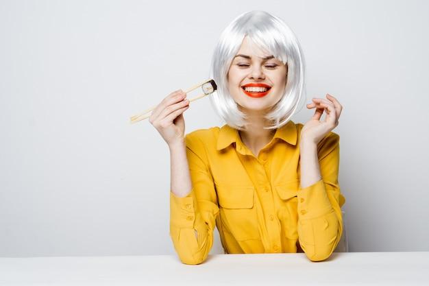 Schönes frauenmodell, das sushi und brötchen von der lebensmittellieferung am tisch in einem gelben hemd isst, das verschiedene emotionen aufwirft