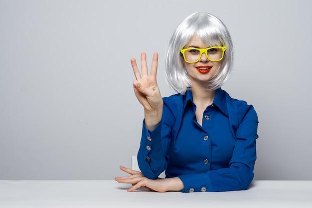 Schönes frauenmodell, das verschiedene emotionen aufwirft. blonde perücke