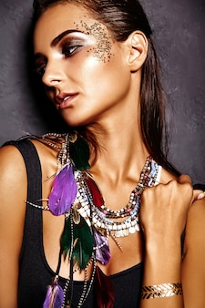 Schönes frauenmodell im sommer schwarze wäsche mit hellem kreativem make-up, das nahe grauer wand aufwirft