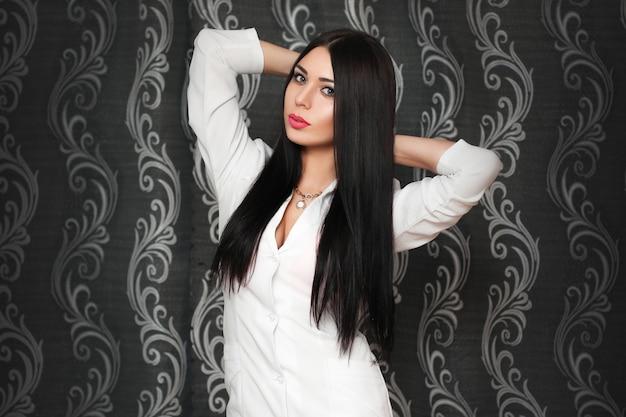 Schönes frauenmodell im weißen hemd auf weinlesehintergrund