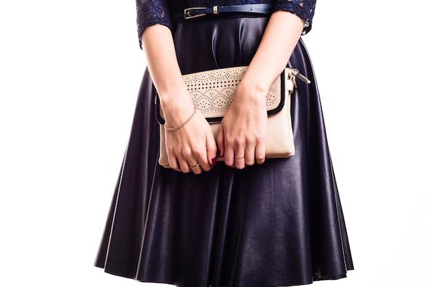 Schönes frauenmodell in einem lederrock hält eine handtasche