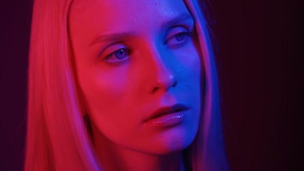 Schönes frauenmodell mit blauen augen, die in neonlichtnahaufnahme aufwerfen. konzept der modefotografie. 4k uhd