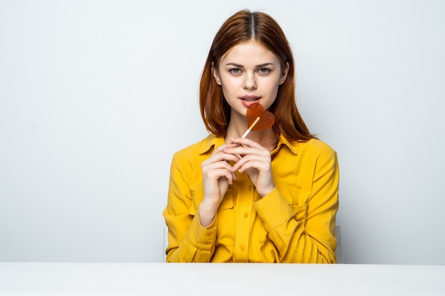 Schönes frauenmodell mit einem herzlutscher am tisch in einem gelben hemd wirft verschiedene emotionen auf. valentinstag