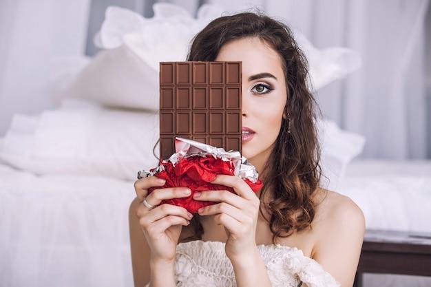 Schönes frauenmodell mit fliesen der dunklen schokolade in den händen gegen schlafzimmerinnenraum