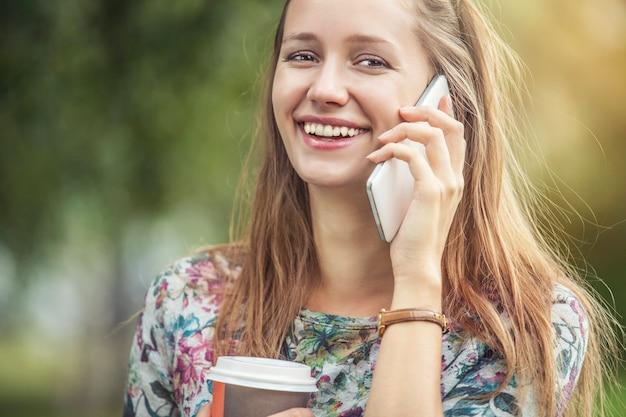 Schönes frauenmodell mit kaffee zum mitnehmen und einem telefon im park. stil, lässig, trinken, glück, sonnig