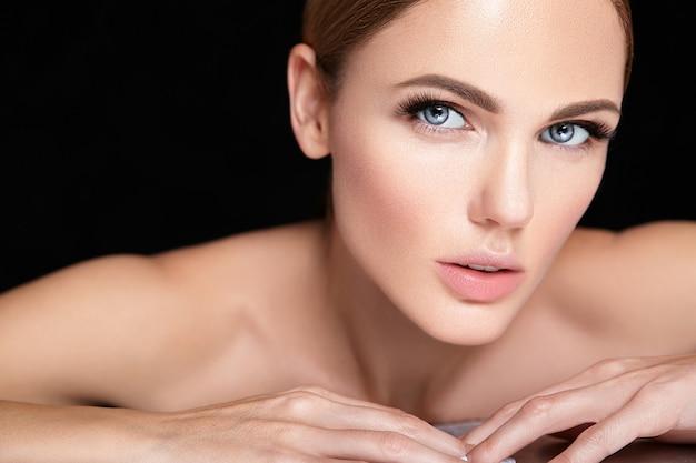 Schönes frauenmodell ohne make-up und sauberes gesundes hautgesicht auf schwarz