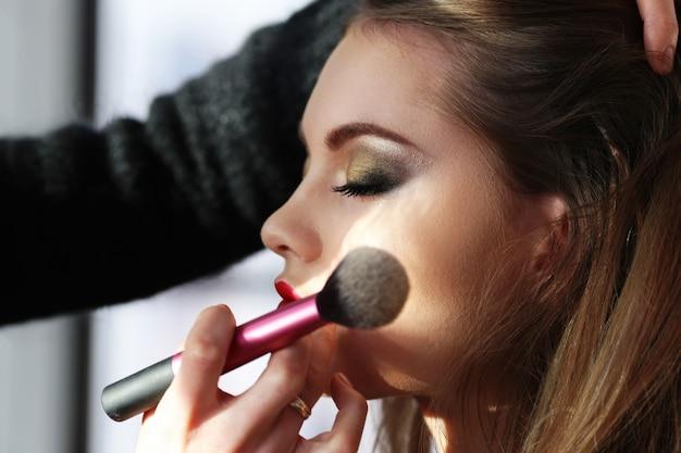 Schönes frauenporträt beim schminken