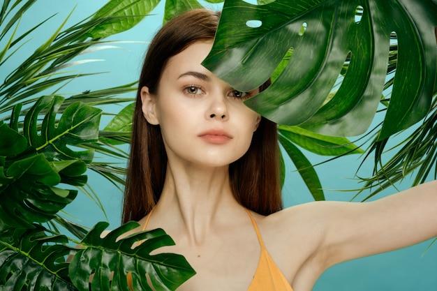 Schönes frauenporträt in palmenbüschen, schöne haut des gesichts